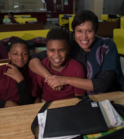 Mayor Bowser hugging kids in their classroom